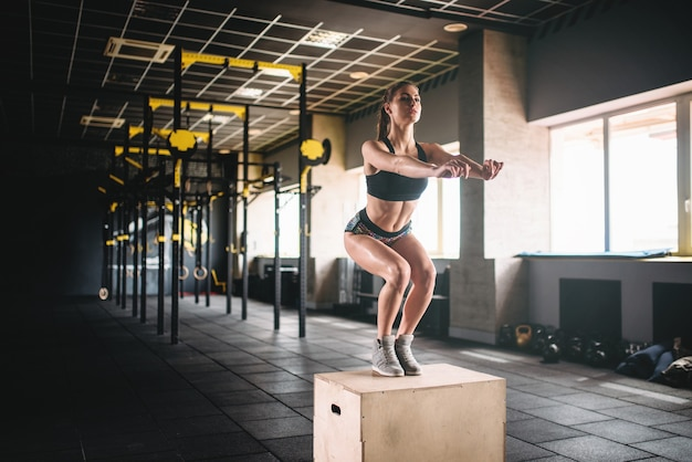 Vrouw doet box jump oefening in fitnessclub