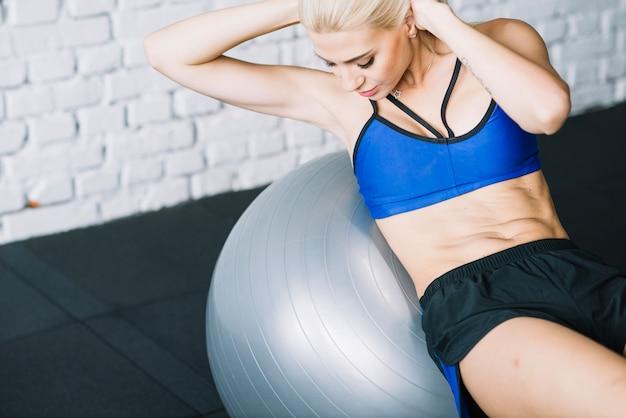 Vrouw doet buik crunches op fitball