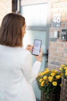 Vrouw doet de deur dicht of zet het huisalarm aan met telefoon