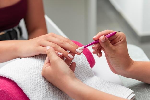 Vrouw doet de manicure van een cliënt