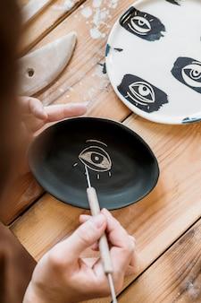 Vrouw doet een aardewerkmeesterwerk in haar atelier