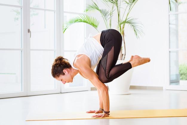 Vrouw doet een bakasana of kraan yoga pose