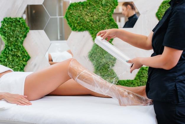 Vrouw doet een cosmetologie procedure volledige lichaamspakking in een moderne schoonheidssalon.