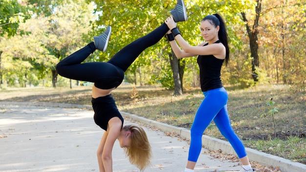 Vrouw doet een handstand op een weg in een park terwijl ze wordt ondersteund door haar teamgenoot tijdens een trainingssessie samen