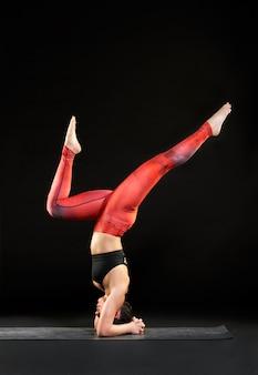Vrouw doet een headstand met pijl en boog benen