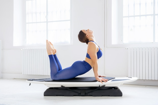 Vrouw doet een upside down dog variant yoga pose op een surfset in een profielweergave in een high key sportschool