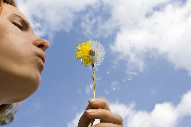 Vrouw doet een wens terwijl ze een bloem blaast