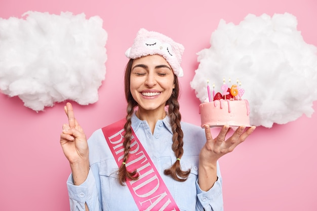 Vrouw doet een wens terwijl ze verjaardagstaart vasthoudt met kaarsen sluit de ogen glimlacht zachtjes kruist de vingers gelooft dat dromen uitkomen draagt een slaapmasker shirt poseert binnen