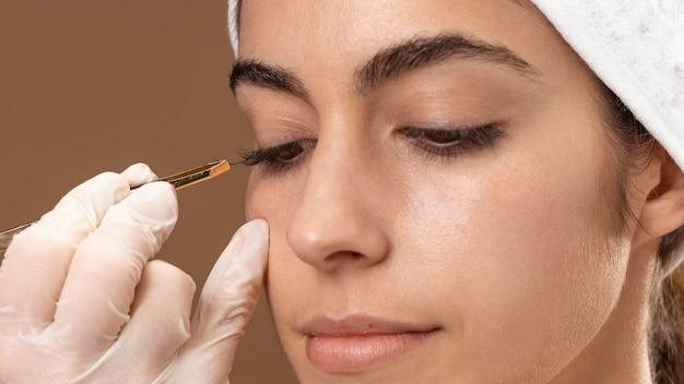 Vrouw doet een wimpersbehandeling aan haar cliënt