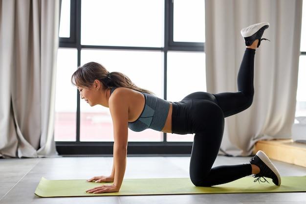 Vrouw doet fitness oefening, thuis training. fitness, training, meditatie, yoga, zelfzorg pilates concept