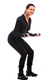 Vrouw doet fitness oefeningen met gewichten