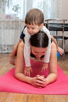 Vrouw doet fitness oefeningen met kind thuis