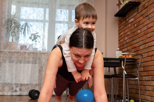 Vrouw doet fitness oefeningen met kinderen thuis