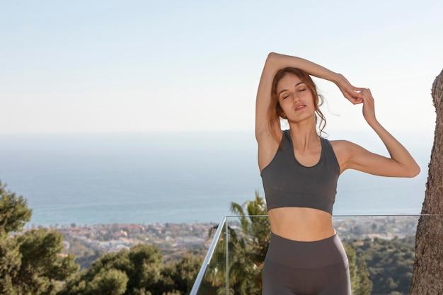 Vrouw doet fitness thuis op balkon