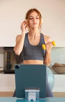 Vrouw doet fitness thuis op de mat