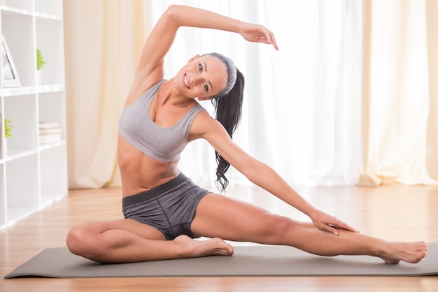 Vrouw doet fitness thuis op haar woonkamer vloer.
