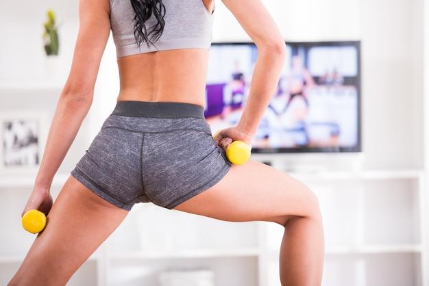 Vrouw doet fitness thuis op haar woonkamer.