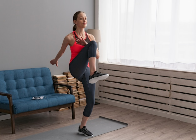 Vrouw doet fitness training thuis en loopt hoge knieën