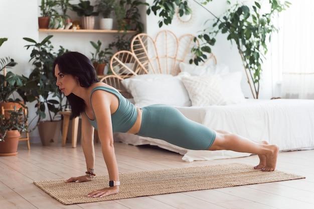 Vrouw doet fitness yoga oefeningen plank thuis