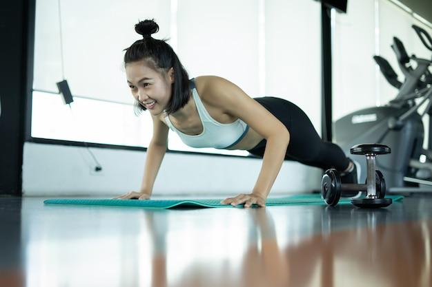 Vrouw doet fitnesstraining. fitness vrouw doet push ups op een trainingsmat. jonge vrouw doet push-ups in de sportschool. gespierde vrouw doet pushups op oefening mat op gymnasium.