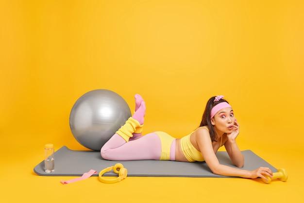Vrouw doet fysieke oefeningen op fitnessmat houdt halter gebruikt fitball voor pilatestraining gekleed in activewear
