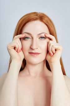 Vrouw doet gezichtsmassage, gymnastiek, massagelijnen en plastic mondogen en neus. massage