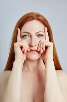 Vrouw doet gezichtsmassage, gymnastiek, massagelijnen en plastic mondogen en neus. massagetechniek tegen rimpels en huidverjonging. , apr