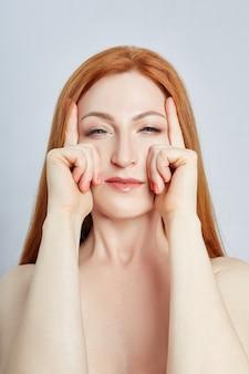 Vrouw doet gezichtsmassage, gymnastiek, massagelijnen en plastic mondogen en neus. massagetechniek tegen rimpels en huidverjonging.