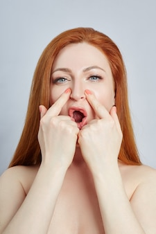 Vrouw doet gezichtsmassage, massagelijnen en plastic mondogen en neus