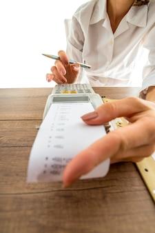 Vrouw doet haar boekhouding op een handmatige rekenmachine met een laag gezichtspunt langs de papieren strook naar haar vingers op de cijfertoetsen.