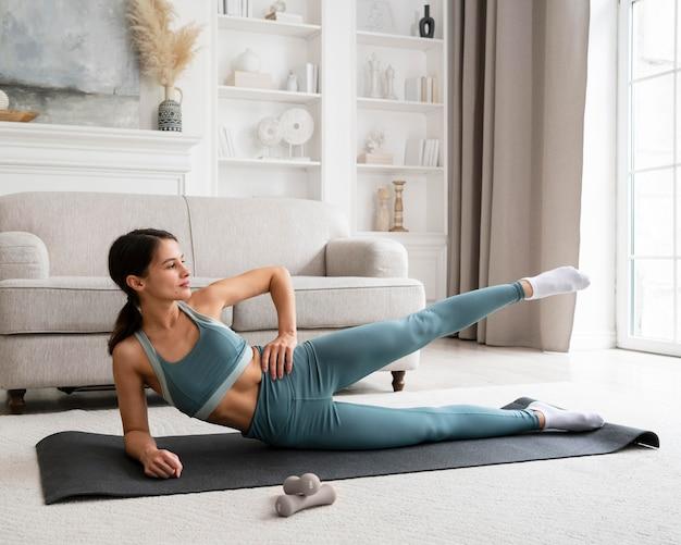 Vrouw doet haar training thuis op een fitnessmat