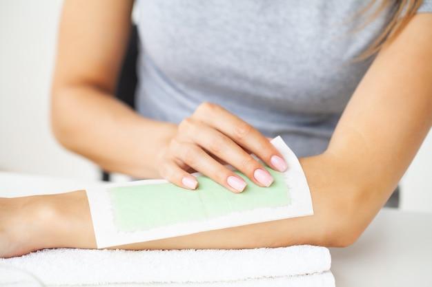 Vrouw doet haarverwijdering op hun handen thuis in de badkamer.