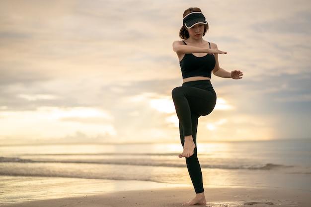 Vrouw doet hoge knie-draai oefening op het strand met zonsopgang op de ochtend.