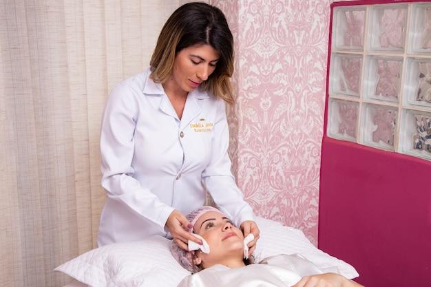 Vrouw doet huidreiniging bij de schoonheidsspecialistekliniek. de huid reinigen. de puistjes uit het gezicht halen