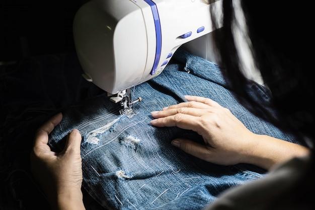 Vrouw doet jeans patchwork met behulp van naaimachine - thuis diy naaien concept
