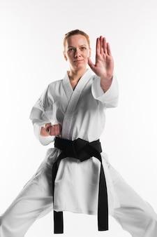 Vrouw doet karate pose vooraanzicht