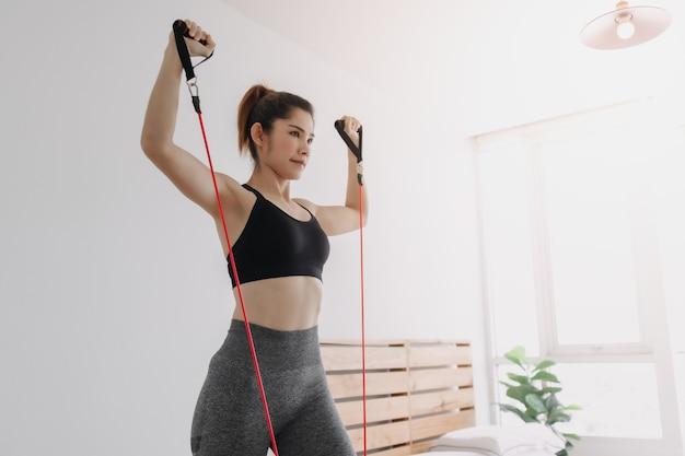 Vrouw doet krachttraining op de bovenste borstpers in haar slaapkamer