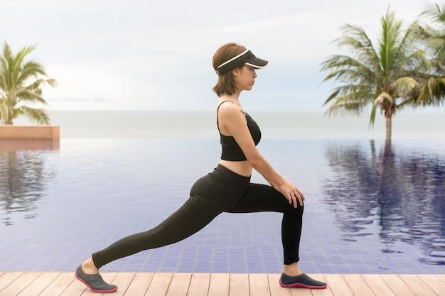 Vrouw doet lage longe oefening op het strand met zonsopgang in de ochtend.
