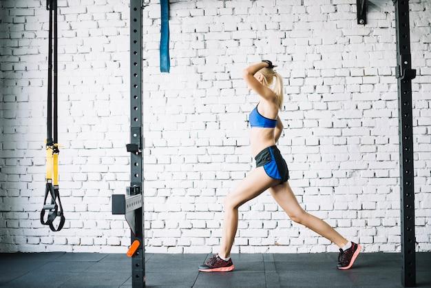 Vrouw doet lunges achter crossfit rek