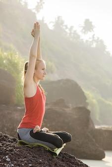 Vrouw doet ochtendyoga en meditatie op het strand dichtbij op de rotsen