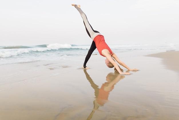 Vrouw doet ochtendyoga op het strand bij de zee met weerspiegeling in het water