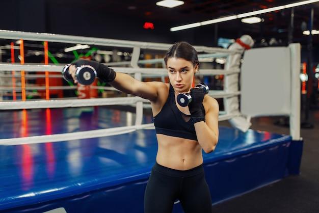 Vrouw doet oefening met halters, bokstraining. vrouwelijke bokser in de sportschool, meisje kickbokser in sportclub, kickboksen training