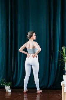 Vrouw doet oefeningen die zich uitstrekt terug armen en benen