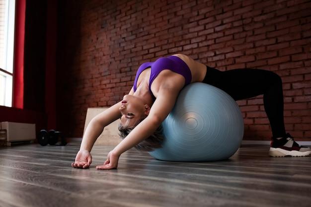 Vrouw doet oefeningen met fitball in fitness gym klas