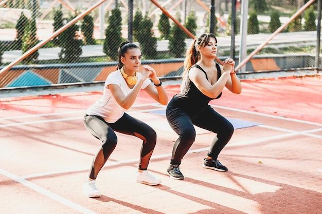 Vrouw doet oefeningen met haar vriendin om af te vallen buiten in een sportpark buiten terwijl u naar muziek luistert.