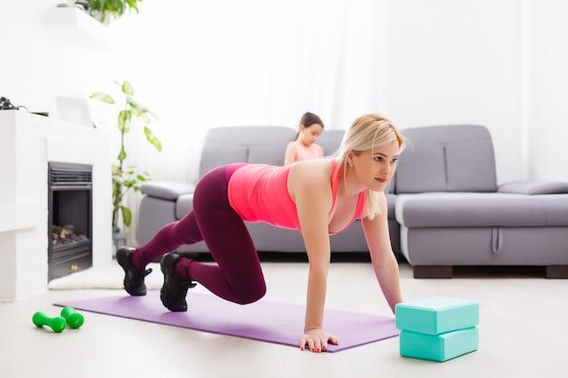 Vrouw doet online yoga met laptop tijdens zelfisolatie in haar woonkamer, geen training van apparatuur, meditatietips voor beginners. familietijd met kinderen, blijf thuis.