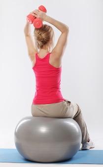 Vrouw doet pilates en evenwichtsoefeningen