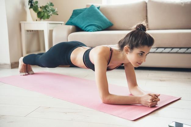 Vrouw doet plank thuis dragen activewear op een yoga tapijt
