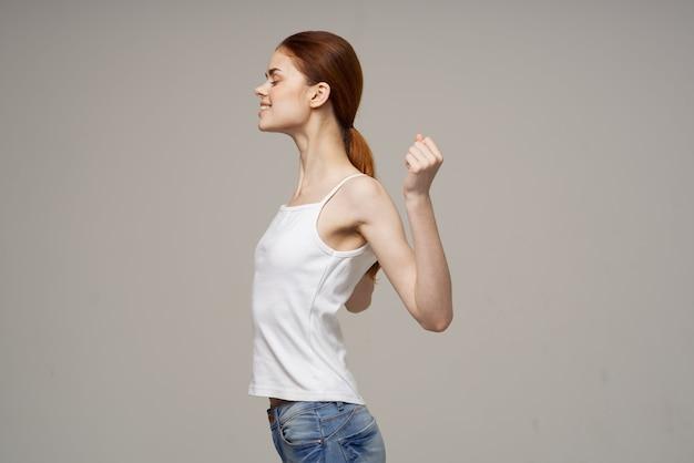 Vrouw doet schouder oefeningen gezondheid grijze achtergrond