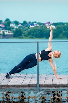 Vrouw doet sportoefeningen op handen op de pier van het meer
